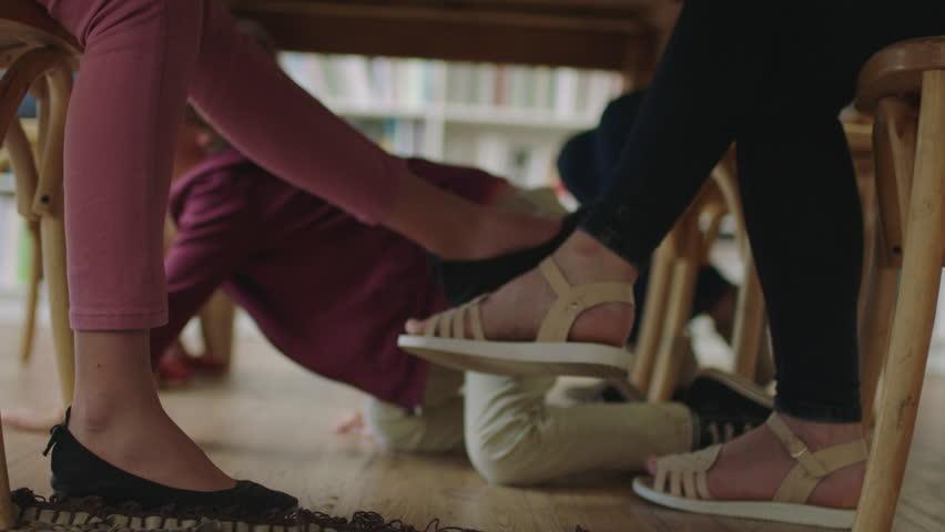 Young little boy sitting under table crawling hiding enjoying playing fun people legs   Shutterstock HD Video #1010187029