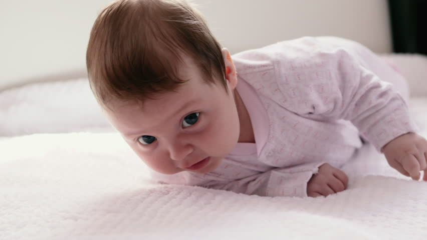 A two-month-old child lies on a bed and rolls from stomach to back   Shutterstock HD Video #1010198849