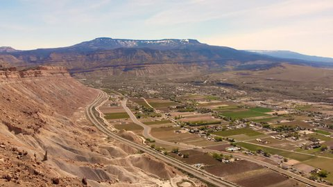 Green agricultural land in the Grand Valley. Filmed by a drone tracking right and pulling back from the Boockliff Mountains in Palisade, Colorado. Looking East from Mount Garfield.