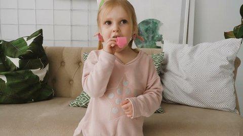 Close-up of little cutey girl wearing festive cap blows horn