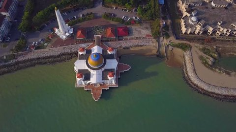 Drone aerial View footage - View of a White Floating Mosque, The Melaka Straits Mosque, located on the man-made Malacca Island near Melaka City, Melaka, Malaysia.