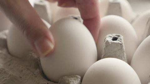 Hand takes one from eggs packed in carton 4K video