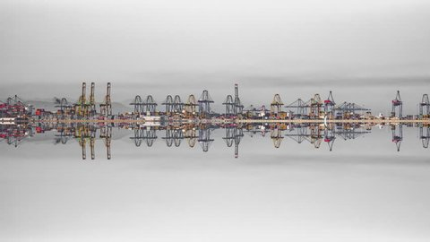Wide panorama Timelapse of port cranes symmetry reflected with gray clouds and text space