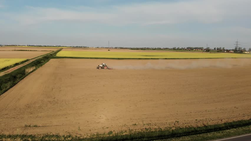 Aerial of tractor on field in dust (top view from side)  | Shutterstock HD Video #1010257559