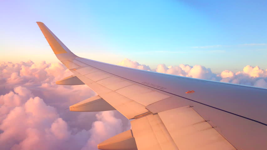 Airplane flight. Wing of an airplane flying above the clouds with sunset sky. View from the window of the plane. Aircraft. Traveling by air. 4K UHD video | Shutterstock HD Video #1010280539