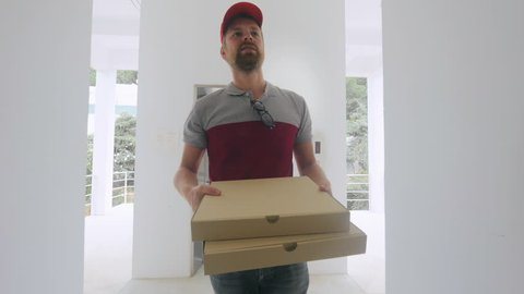 Smiling pizza delivery man delivering pizzas in the stylish house. Worker takes the lift, view from the bottom.
