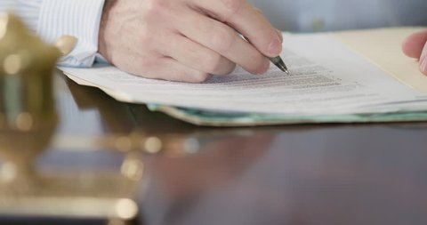 A close up shot of the hand of Caucasian male businessman or lawyer wearing cuff links and writing on a legal document with a fountain pen.