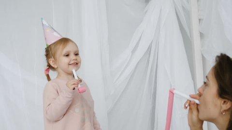 Slow motion shot of little cutey girl wearing festive cap blows horn