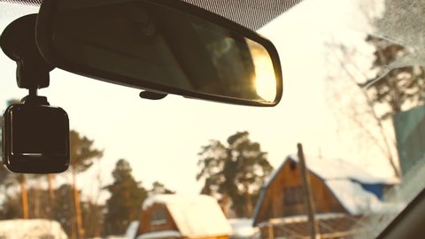 Driving car in winter countryside in slow motion. Sunset sun in rear view mirror