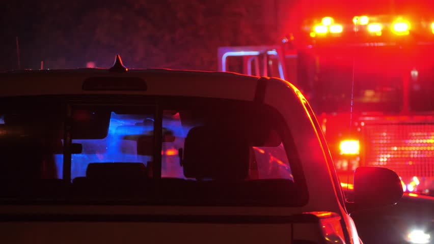 Flashing red  and blue emergency lights  seen through car's interior silhouette at night. Fire truck in background. 4K UHD.   Shutterstock HD Video #1010326259