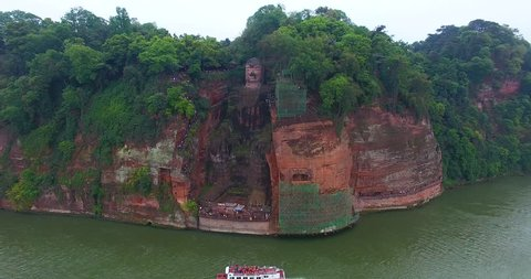 Aerial drone view of the impressive giant Buddha statue in Leshan, tourist view the site on boat, China, 4k