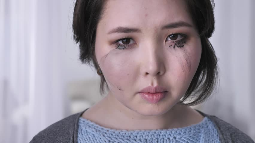 Portrait of a young busty asian brunette girl, crying, looking at the  camera, smudged makeup 50 fps