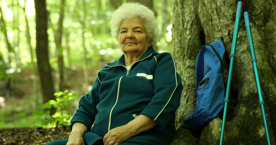 Old Woman Tourist Presentation Serious Look Camera Sitting on Ground Wood Trunk