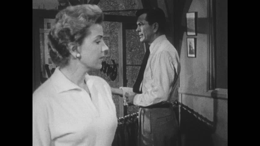1950s: UNITED STATES: lady and man talk in office. Man rolls up sleeves. Man looks through glass window