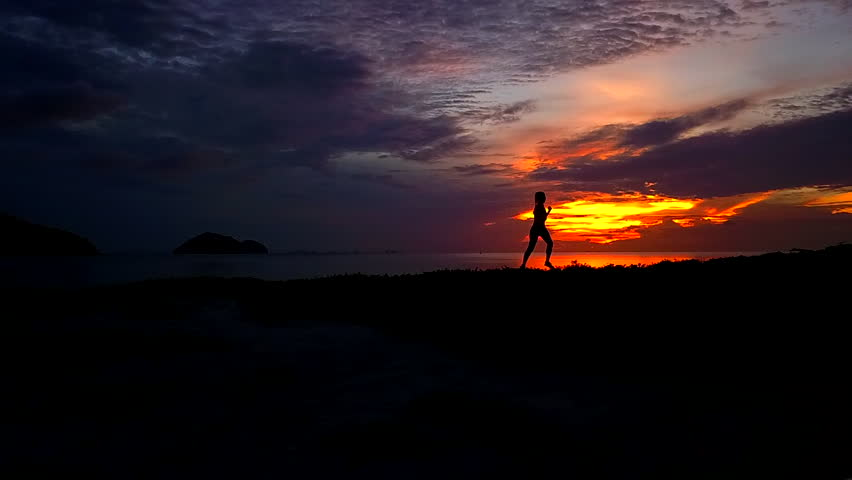 Tracking shot of woman silhouette jogging on the beach after sunset time.Fitness sport girl jogging fast training cardio near sea. Fly cam slow motion video #1010363939