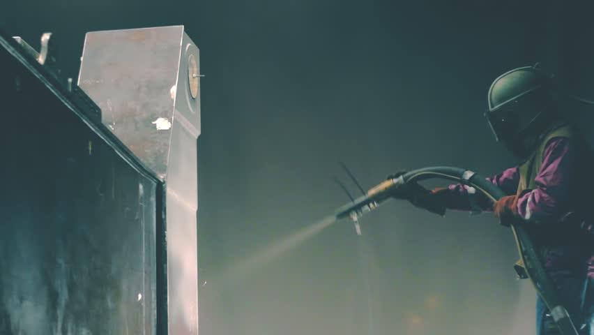 Industrial worker cleans metal surface by sandblaster gun