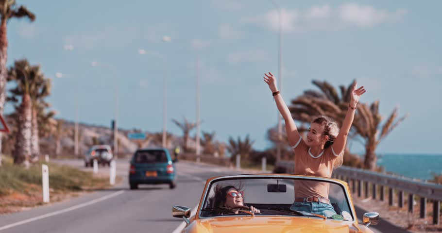 Young women having fun driving convertible vintage car on exotic island palm tree seaside road #1010364359