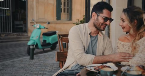 Young happy couple drinking coffee and having brunch at traditional cafe in Europe