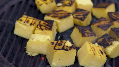 Closeup of polenta on a grill with smoke rising.
