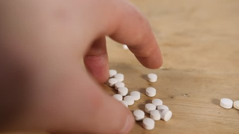 Slow motion drug white pills falling onto wooden table from mans hand onto wooden table for headache prescription tablets