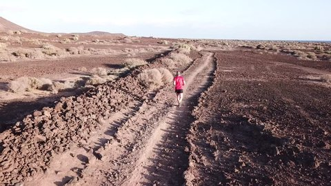 Aerial view of young man running alone through desert to nowhere. Runner enjoying a trail session in a lonely spot in Tenerife, Canary Islands.