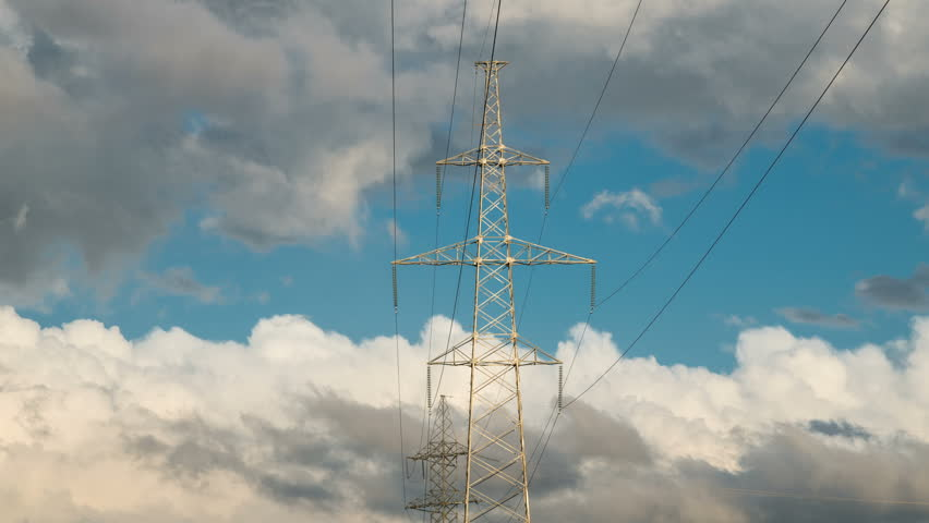 High voltage electricity tower pylons and transmission power lines on the cloudy sky background. Timelapse 4K