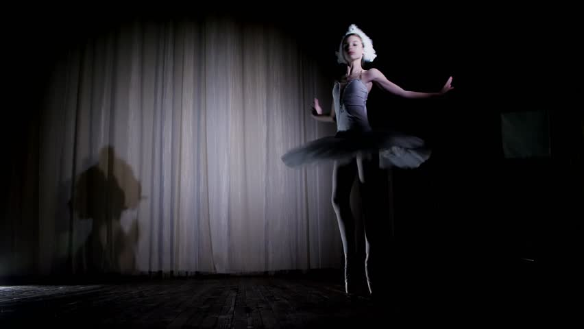 in rays of spotlight, on the stage of the old theater hall. Young ballerina in suit of white swan and pointe shoes, dances elegantly certain ballet motion, Swan Lake