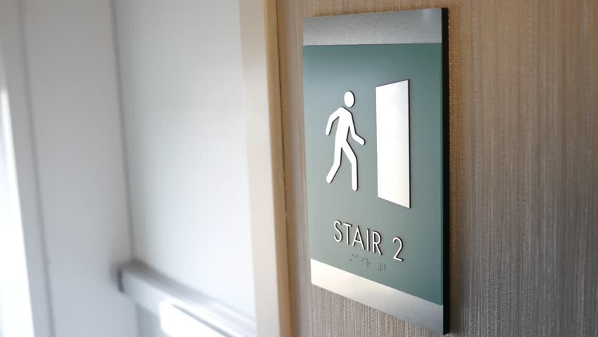Man enters a stairwell in modern building - sign close up