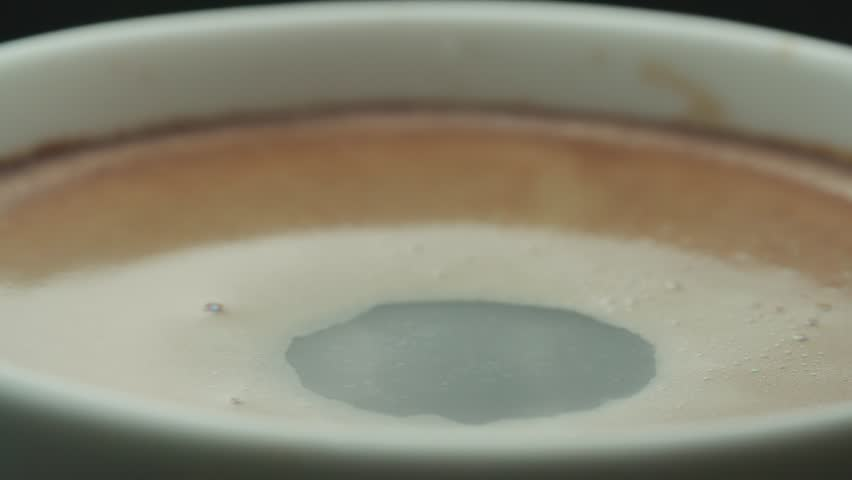 last drop of coffee falls into the filled Cup from the coffee machine in slow motion