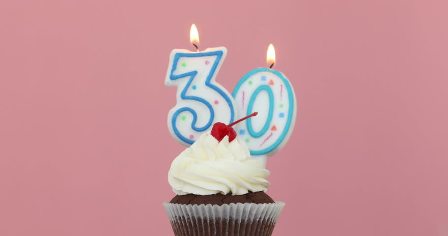 Number thirty 30 candle in a cupcake against a pastel pink background blow out at the end