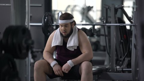 Funny overweight male pretending to be muscular and strong in gym, insecurities