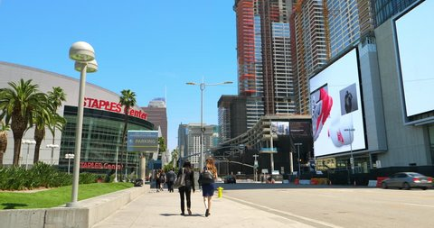 LOS ANGELES, CALIFORNIA, USA - APRIL 22, 2018: Construction boom at development site and people walking near NBA Staples Center and electronic digital billboards in Los Angeles, California, USA, 4K