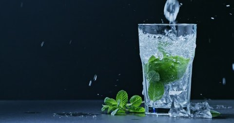 In a glass pour a cold drink with mint, lime and ice . Slow motion 2k video shooted on 240 fps