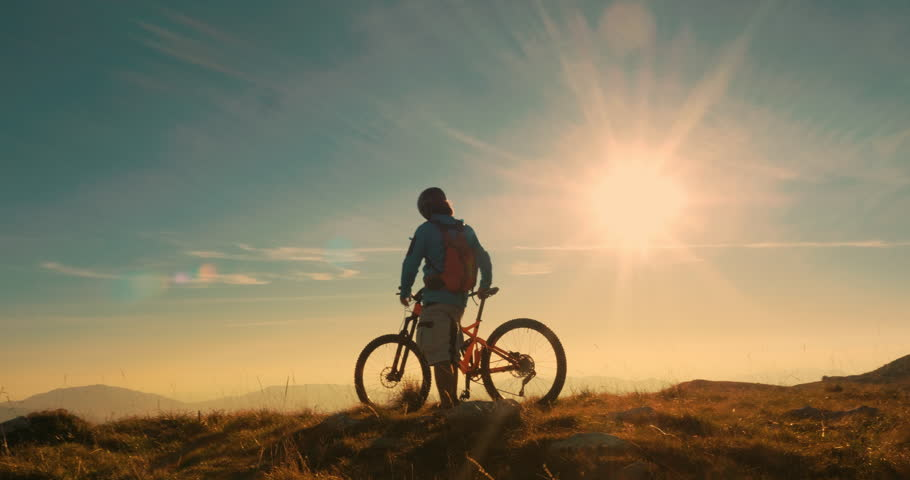 Mountain biker reaching the top celebrating with lifting his bike to the sky in amazing evening light. | Shutterstock HD Video #1010578229