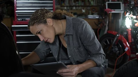 Mature woman referencing mobile tablet and working on motorbike, smiling at camera.
