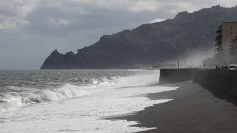wind storm and clouds on the beach of Taormina with the fortress of Sant'Alessio Siculo in the background among water clouds