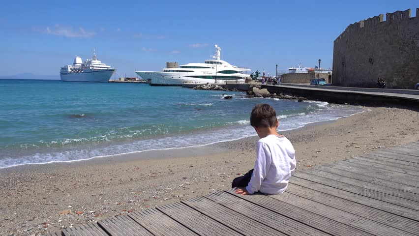Rhodes, Greece - 21st of April 2018: 4K Boy sits opposite to Rhodes seaport
