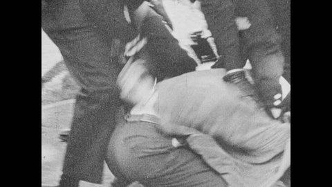 1960s: UNITED STATES: police push protestors to ground during strike action. Police arrest protestors. Police man with baton