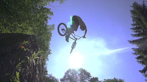 SLOW MOTION: Bmx biker jumps over the sun