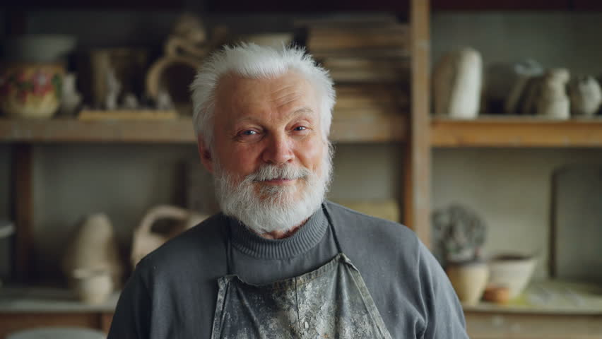 Close-up portrait of senior potter in muddy apron standing at table in workshop and looking at camera. Shelves with handmade vases and pots in background. | Shutterstock HD Video #1010634839
