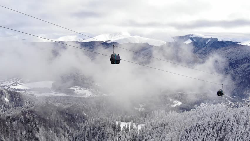 Aerial view over snowy mountain ridge valley with clouds, cable car lifting. Outdoor snow alpine wild nature tourist gondola transportation in winter. High altitude gondola in winter. Ski Gondola | Shutterstock HD Video #1010638769