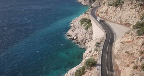 Forward aerial drone video follow cars over highway road along cliff to reveal Kaputas Beach and Turquoise Coast water near Kas, Turkey. 4k at 23.97fps