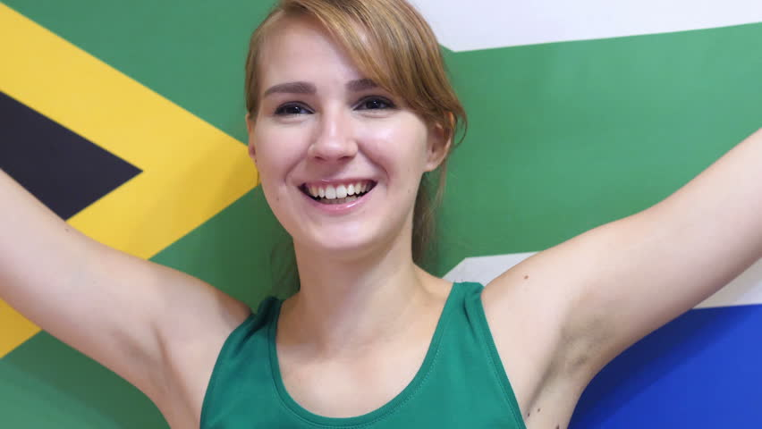 South African Young Woman celebrating while holding the flag of South Africa in Slow Motion