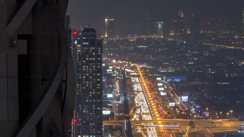 Traffic on the Sheikh Zayed road near business bay. Dubai Downtown skyscrapers night timelapse modern towers panoramic view from the top in Dubai, United Arab Emirates.