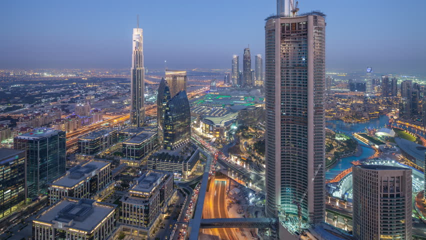 Dubai Downtown day to night transition timelapse modern towers panoramic view from the top in Dubai, United Arab Emirates. Traffic on the road and music fountain