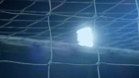 Background of football/soccer/sports stadium lights agains dark sky, net in front, 4k