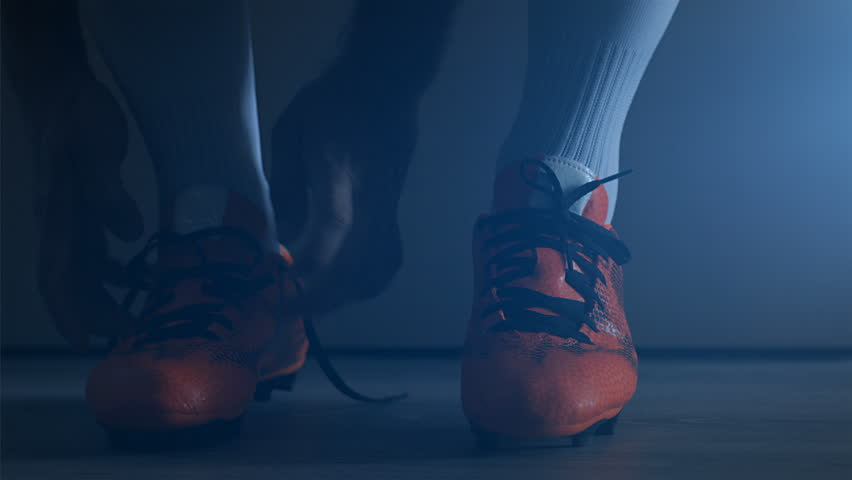 Soccer football player put on his shoes. Slow Motion.