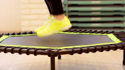 Closeup woman feet legs in sneakers on a trampoline jumping  in the gym healthy strong sport , happiness fitness fit activity