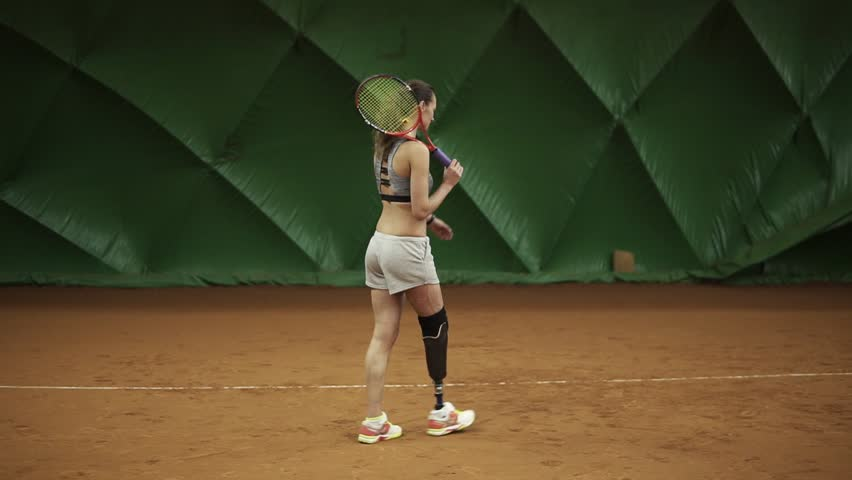 Disabled young woman is walking through the tennis court with racket. Stands in the stance. Ready for match