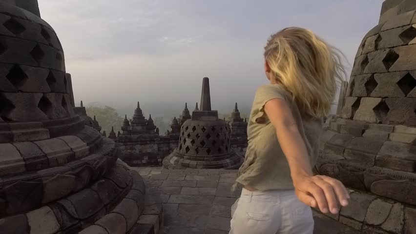 SLOW MOTION video of travel girl embracing sunrise at Borobudur temple, Indonesia . People discovery Asia concept